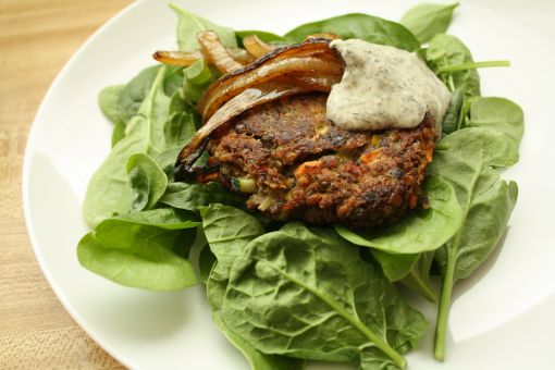 lentil croquette on spinach salad
